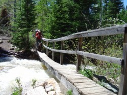 Hiker Skip Whitman and George cross the 1st backcountry bridge at Shingle Creek in the Uinta Mountains.