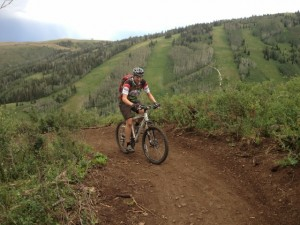 Mason Diedrich mountain bikes up the Pinecone Ridge Trail at one of the few openings where you can get a view. (Photo: Jared Hargrave - UtahOutside.com)