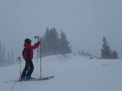 A ski patroller marks hazards using bright orange rope and poles.