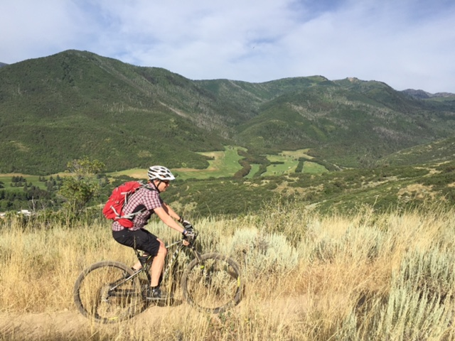 The WOW Trail begins in scrub oak and grassy, exposed terrain. Here, Mason Diedrich tops out onto the ridge, with the Wasatch Mountain State Park golf course below. (Photo: Jared Hargrave - UtahOutside.com)